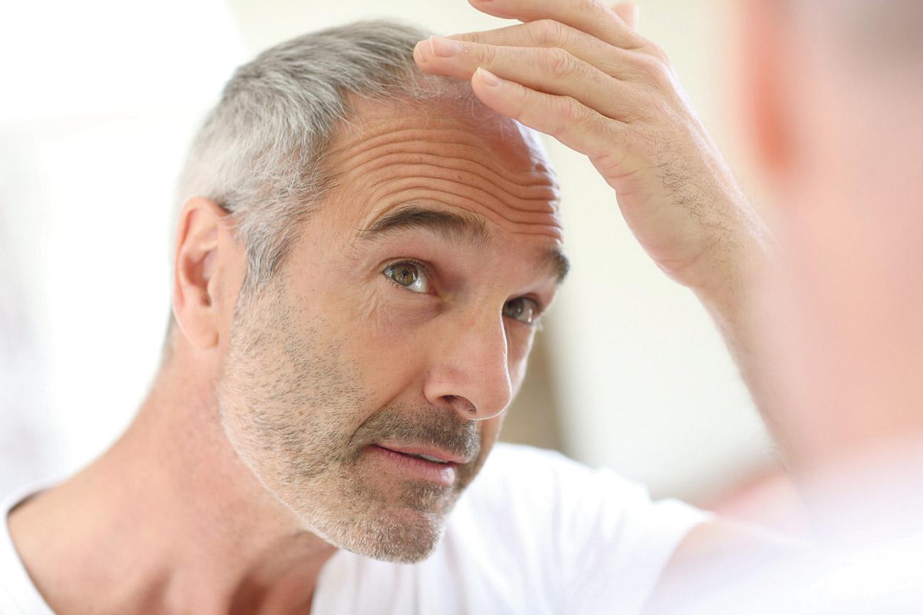 Mann, der sein Haar betrachtet.