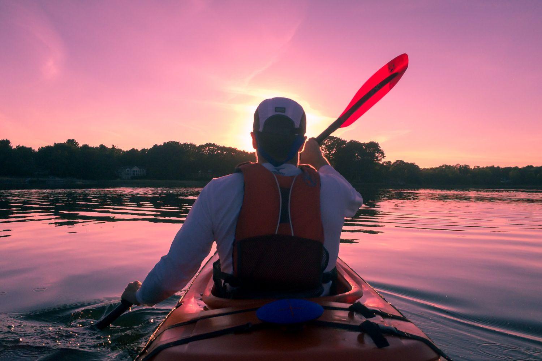 Ein Mann fährt Kajak auf einem See