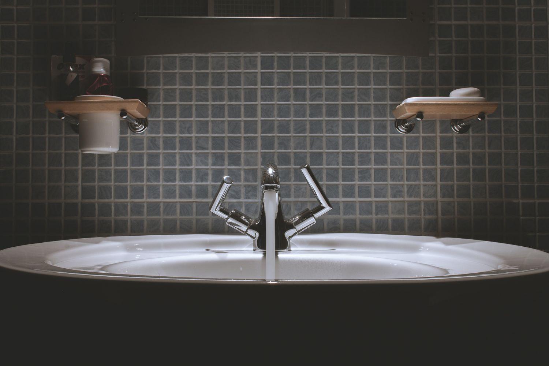 Waschbecken in einem dunkel gefliesten Badezimmer