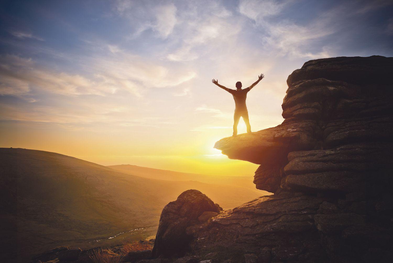 Ein Mann steht bei Sonnenuntergang auf einem Fels