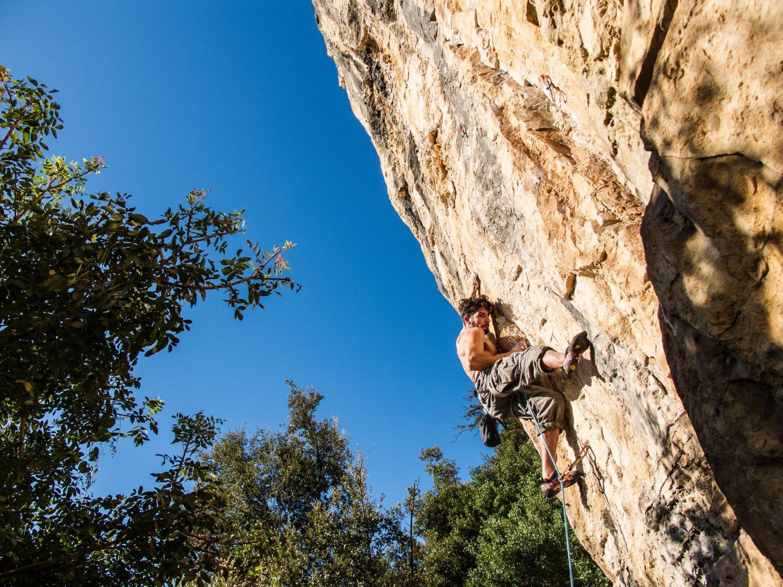 Mann klettert eine Felswand hoch
