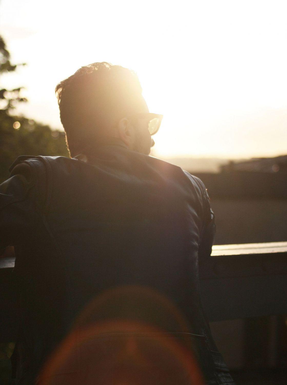 Rückenansicht eines Mannes vor einem Sonnenuntergang