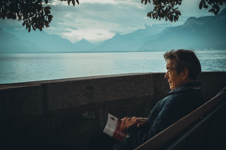Ein älterer Mann blickt auf einen See